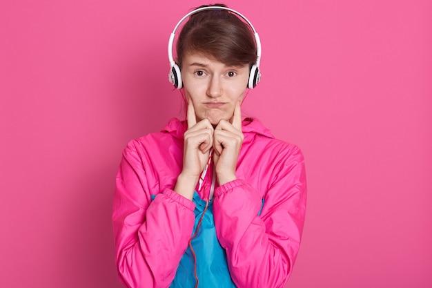 Het studioschot van jong vrolijk kaukasisch sportief meisje in sportwear met witte hoofdtelefoon op hoofd, luisterend aan muziek, kijkt verstoord