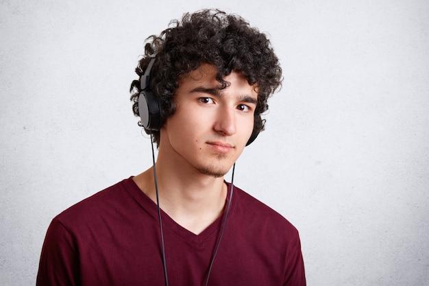 Het studioschot van mannelijke tiener luistert muziek in moderne hoofdtelefoons