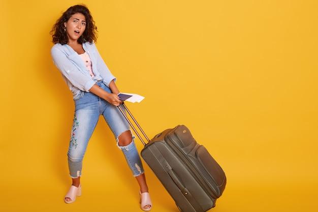 Het studioschot van mooi meisje draagt zware koffer met in hand documenten en vliegtickets