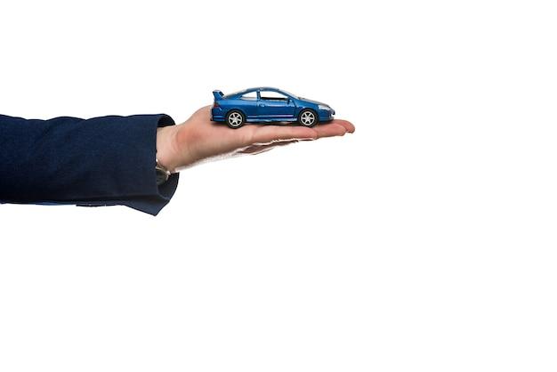Het stuk speelgoed auto van de zakenmangreep en ons geld voor verkoop of huurauto die op wit wordt geïsoleerd