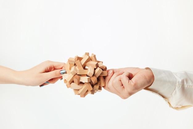 Het stuk speelgoed houten raadsel in handen die op witte achtergrond worden geïsoleerd