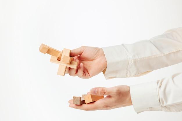 Het stuk speelgoed houten raadsel in handen solated op witte achtergrond