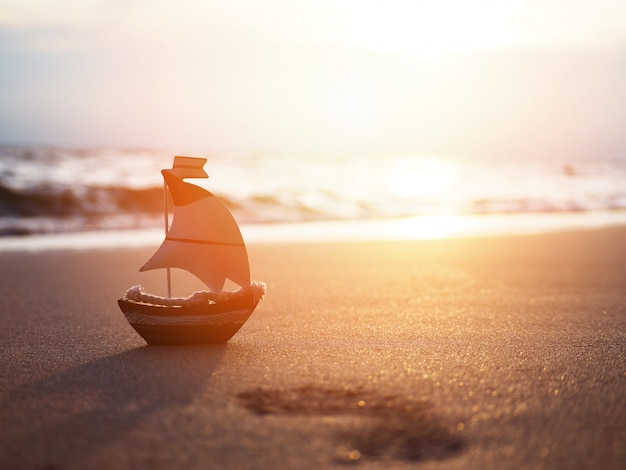 Het stuk speelgoed van de silhouetkleine boot op zand bij zonsondergangstrand.