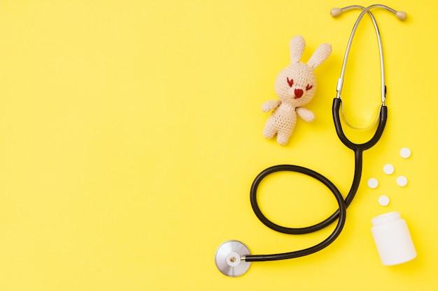 Het stuk speelgoed van kinderen amigurumi met stethoscoop op gele achtergrond met exemplaarruimte.