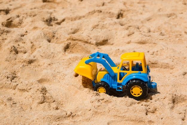 Het stuk speelgoed van kinderen graafwerktuig in het zand