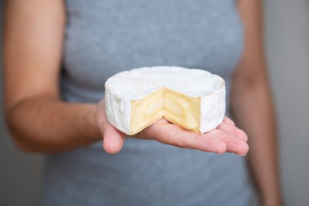 Het stuk van de vrouwenholding van zachte kaas op palm