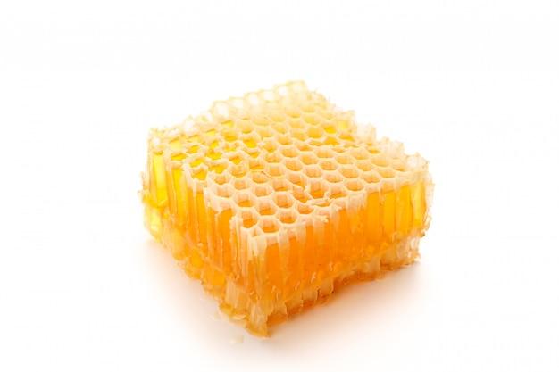Het stuk van honingraat op witte achtergrond wordt geïsoleerd die, sluit omhoog