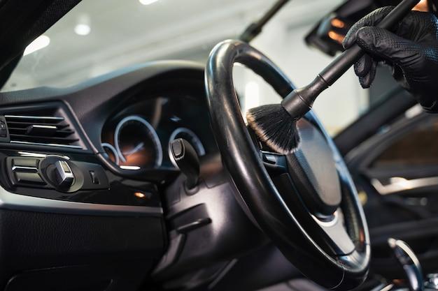 Het stuur van de auto met een borstel reinigen van vuil
