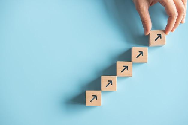 Het succesproces van de bedrijfsconceptengroei, sluit omhoog vrouwenhand schikend houtsnede het stapelen als staptrede op document blauwe achtergrond, exemplaarruimte.