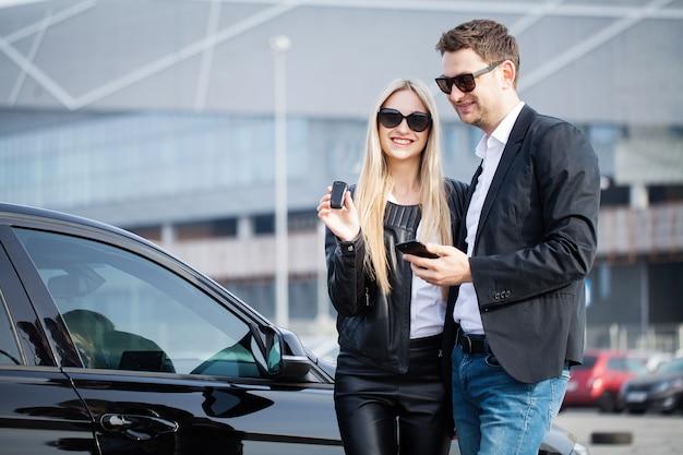 Het succesvolle bezoek aan de dealer. het gelukkige jonge paar kiest en het kopen van een nieuwe auto voor het gezin