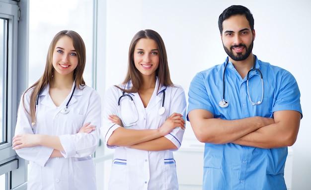 Het succesvolle team van artsen bekijkt camera en glimlacht terwijl status in het ziekenhuis