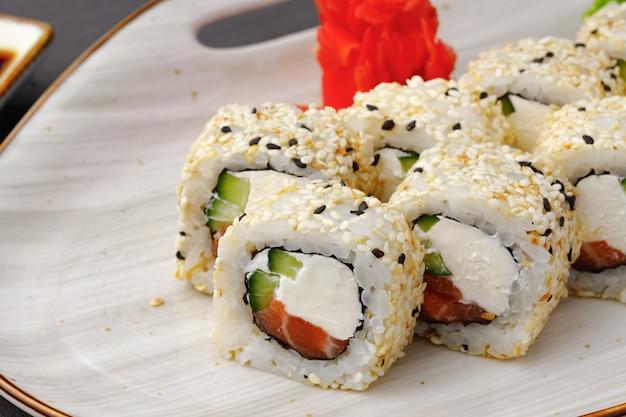 Het sushibroodje met zalm, de kaas van philadelphia en sesam op plaat sluit omhoog Premium Foto
