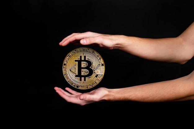 Het symbool van de nieuwe populaire cryptocurrency bitcoin met de afbeelding van handen