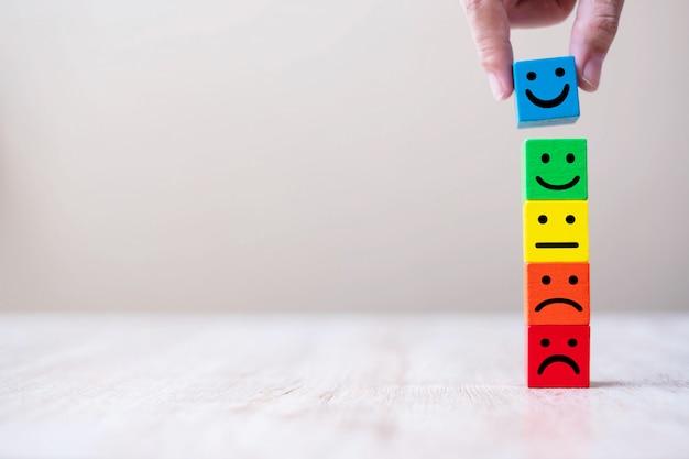 Het symbool van het emotiegezicht op houten kubusblokken. serviceclassificatie, ranking, klantbeoordeling, tevredenheid en feedbackconcept.