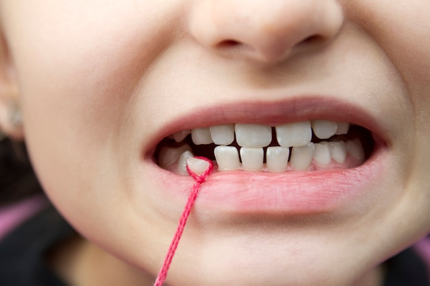 Het tandje van een baby uit een meisje trekken met een rood koord