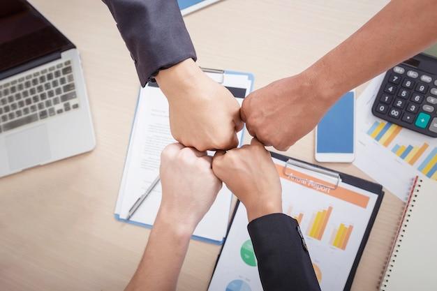 Het team van bedrijfsmensen die handen ineen bij elkaar brengen die teamworksamenwerking en eenheid tonen.
