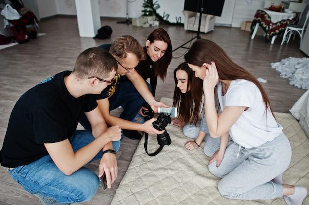 Het team van fotografen toont foto's op het scherm van de camera voor tweeling modellen meisjes op studio. professionele fotograaf op het werk.