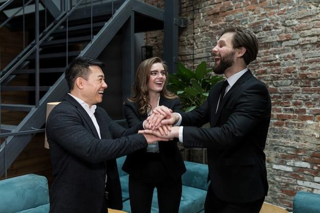 Het team van medewerkers houdt elkaars hand vast