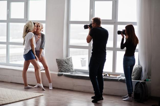 Het team van twee fotografen die een tweeling fotograferen, modelleert meisjes op studio tegen grote ramen. professionele fotograaf op het werk.