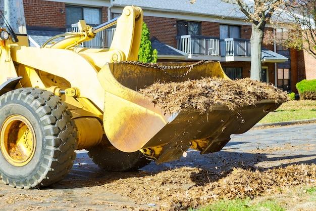 Het teamwerk aan stadsverbetering, het schoonmaken van herfstbladeren in de gevallen bladeren met een tractor