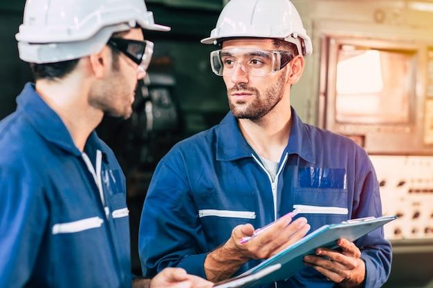 Het teamwerk van de ingenieur werkt met arbeider samen om fabrieksmachine te controleren