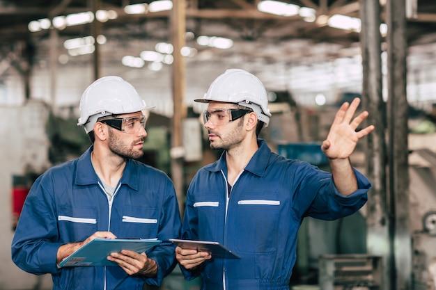 Het teamwerk van de ingenieur werkt met arbeider samen om fabrieksmachine voor veiligheid te controleren en samen te spreken.