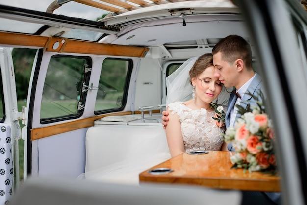 Het tedere jonge huwelijkspaar stelt in een oude bus