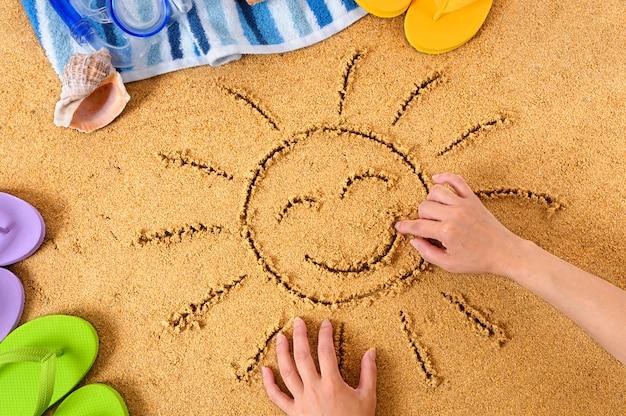 Het tekenen van een gelukkige zon op het strand
