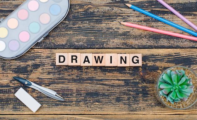 Het tekeningsconcept met houten kubussen, installatie, schoollevering op houten vlakte als achtergrond lag.