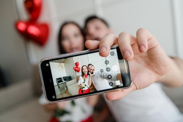 Het telefoonscherm met selfie van man en vrouw in de telefoonzitting van de liefdeholding op laag thuis