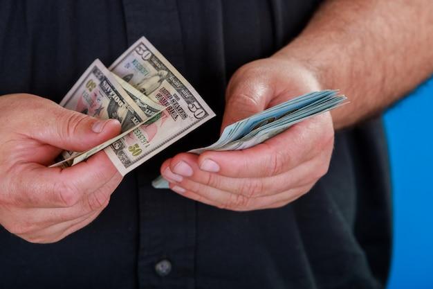 Het tellen van amerikaanse valuta man telt geld. nieuwe dollars in handen close-up bekijken. bedrijf