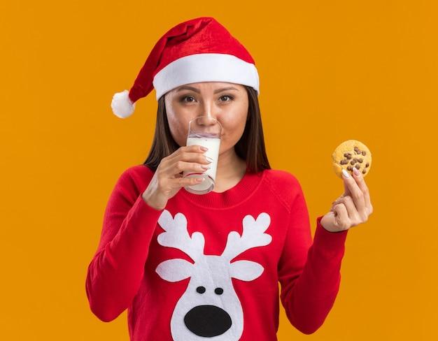 Het tevreden jonge aziatische meisje dat kerstmishoed met de koekjes van de sweaterholding draagt en drinkt melk die op oranje achtergrond wordt geïsoleerd