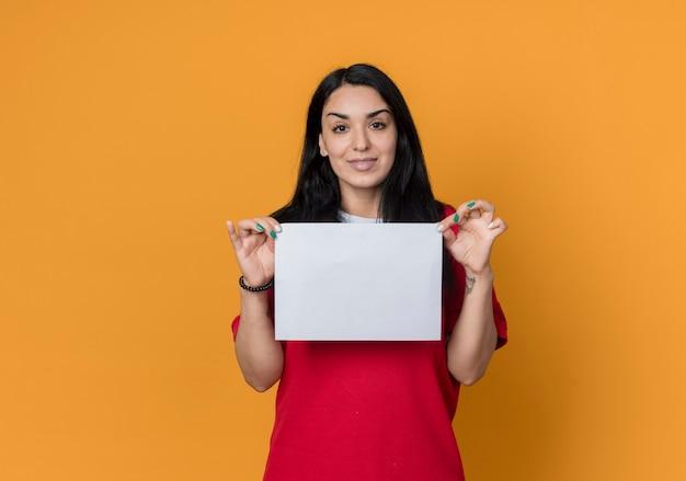 Het tevreden jonge donkerbruine kaukasische meisje dat een rood overhemd draagt, houdt een papieren blad op zoek geïsoleerd op een oranje muur