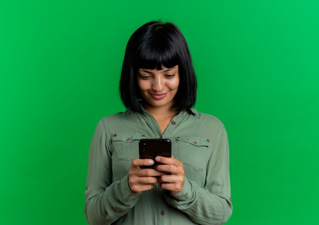Het tevreden jonge donkerbruine kaukasische meisje houdt en bekijkt telefoon