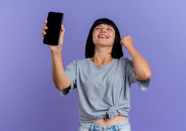 Het tevreden jonge donkerbruine kaukasische meisje houdt telefoon en heft vuist op