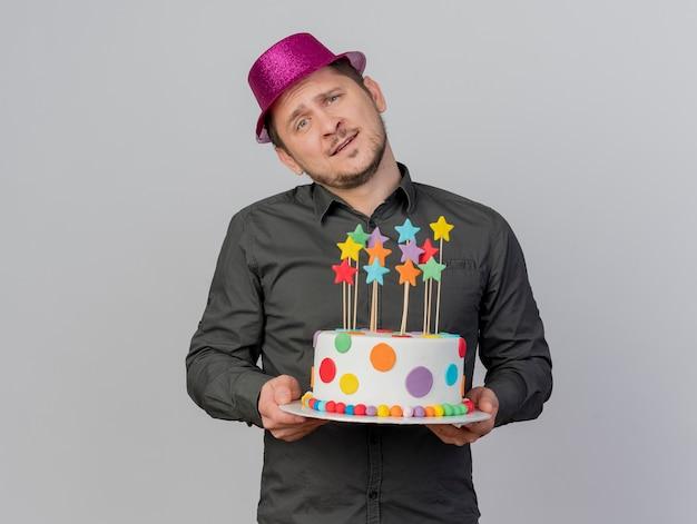 Het tevreden jonge kantelende hoofd van de partijkerel die de roze cake van de hoedenholding draagt die op witte achtergrond wordt geïsoleerd