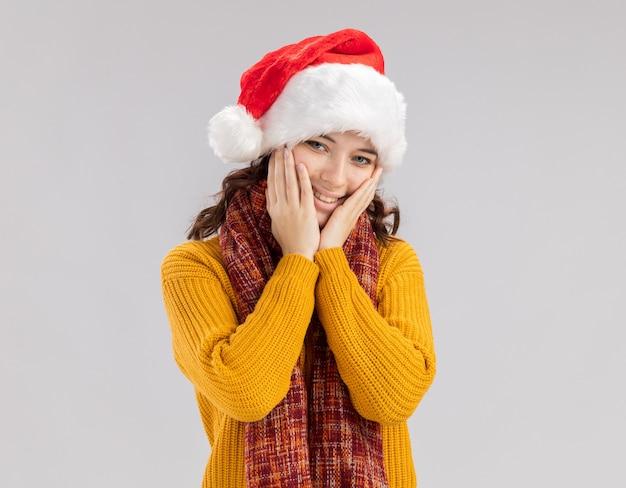 Het tevreden jonge slavische meisje met santahoed en met sjaal om hals legt handen op gezicht