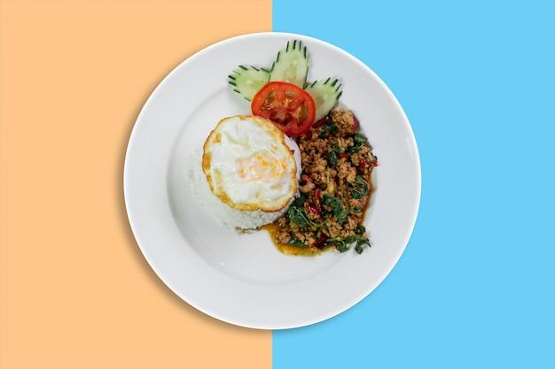 Het thaise kruidige varkensvlees van het voedselbasilicum dat met rijst en gebraden ei wordt gebraden
