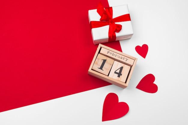 Het thema van de valentijnskaartendag met houten blokkalender, gift en harten
