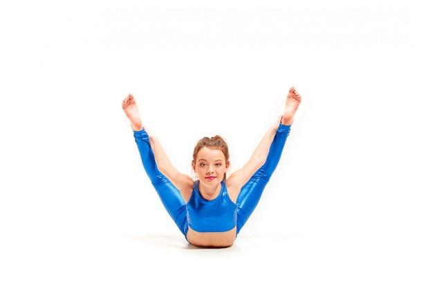 Het tienermeisje dat gymnastiekoefeningen doet die op witte achtergrond worden geïsoleerd