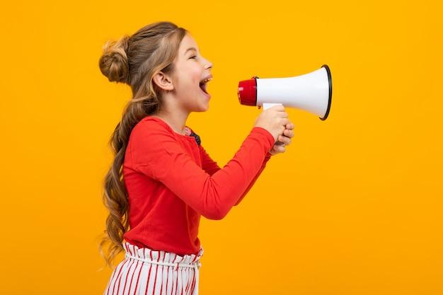 Het tienermeisje het gillen nieuws in een luidspreker en bevindt zich zijdelings op een gele studio met exemplaarruimte