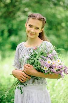 Het tienermeisje houdt een boeket van bloemen in haar handen.