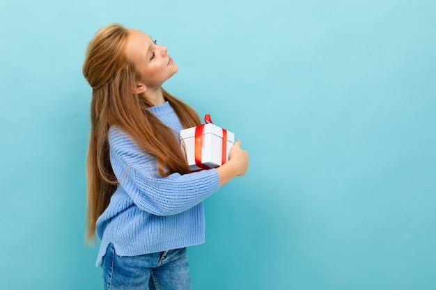 Het tienermeisje houdt een gift met een rood lint in haar handen en bekijkt een muur in lichtblauw