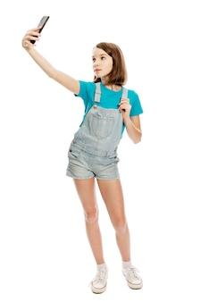 Het tienermeisje in denimoveralls en een blauw t-shirt maakt selfie op een smartphone. bloggen en online communicatie. . volledige hoogte. verticaal.