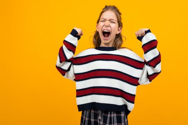 Het tienermeisje in een gestreepte sweater met wijd open mond en opgeheven wapens schreeuwt het nieuws op een gele studioachtergrond met exemplaarruimte
