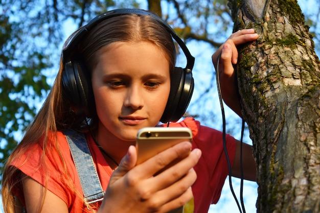 Het tienermeisje in hoofdtelefoons bekijkt telefoon.