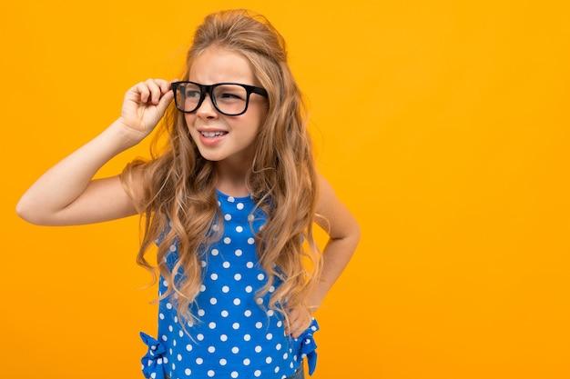 Het tienermeisje loenste in glazen op een geel met exemplaarruimte