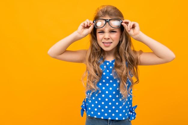 Het tienermeisje loenste in glazen op een gele achtergrond met exemplaarruimte