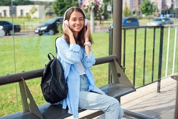 Het tienermeisje luistert naar de muziek door witte hoofdtelefoons in een openbaar vervoerpost terwijl zij op tram wacht.