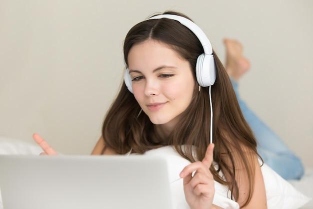 Het tienermeisje luistert online en kiest en koopt liedjes